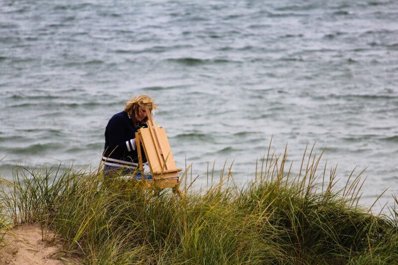 Picture of someone painting at an easel. Painting and arts and crafts are recommended for those suffering from dementia.