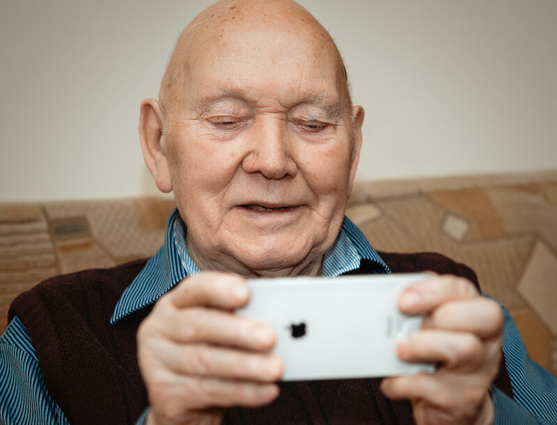 An elderly gentlement engaged in a mobile phone based lockdown activity