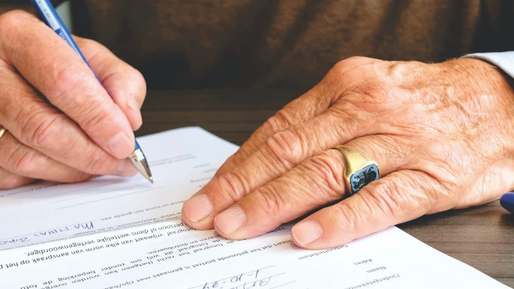 Elderly person signing that they took part in the creation of their care plan
